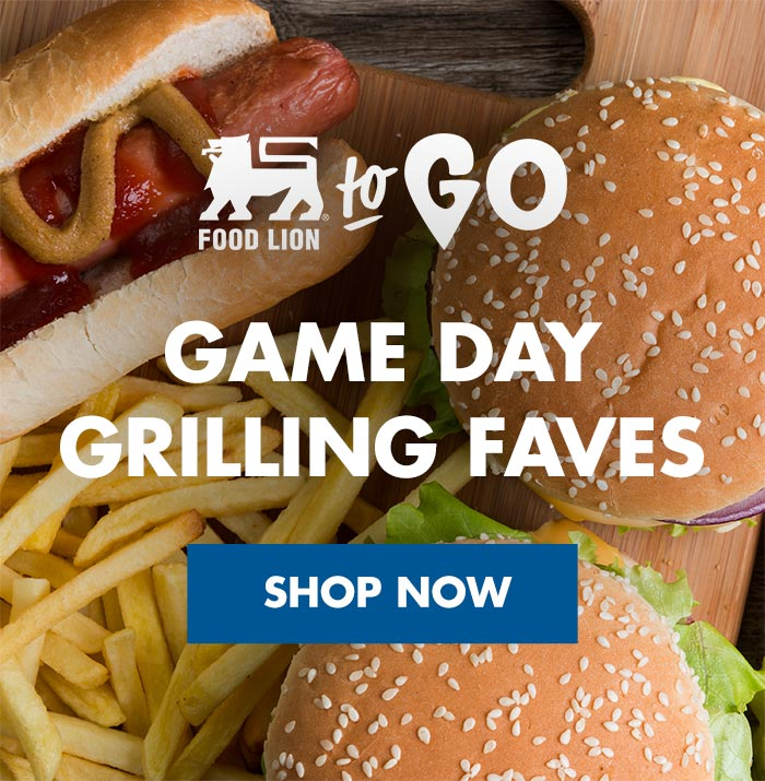 Game day grilling faves, cutting board, hamburgers with sesame seed buns, onions, lettuce, cheese, french fries, hotdog with ketchup and mustard, rustic wood table, Food Lion To Go logo
