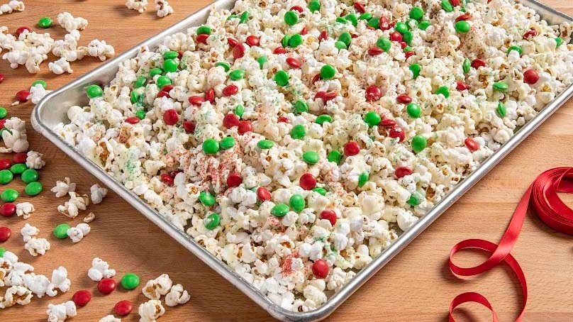 Christmas Crunch Popcorn on baking sheet, red ribbon,, wood table