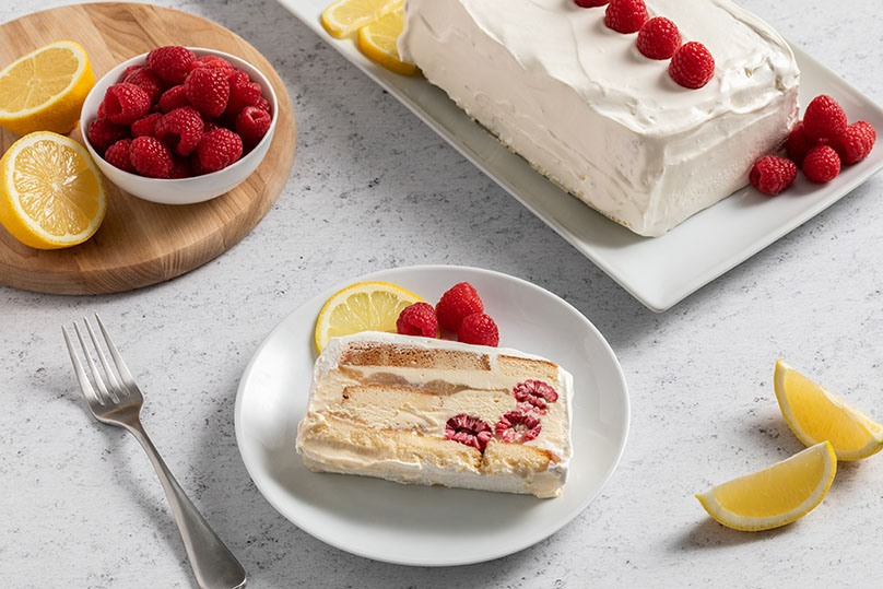 Raspberry Lemon Icebox Cake slice with fresh raspberries and lemon slice on white plate, cutting board with bowl of raspberries, 2 halves of lemon, serving dish with entire icebox cake, fork, on white stone counter