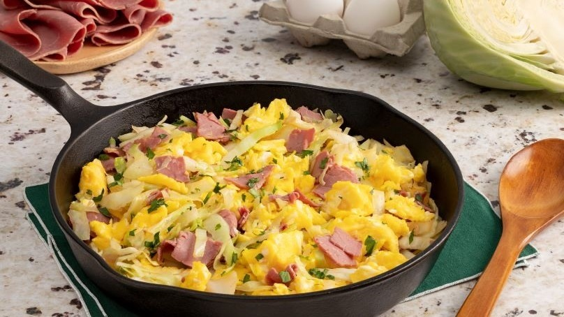 One-Skillet corned beef and cabbage scramble, wooden spoon, head of cabbage in background with carton of eggs and plate of corned beef, white stone counter