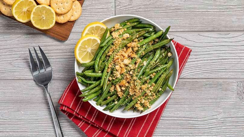 Roasted Green Beans with with toasted cracker crumbles and sliced lemons on a plate, red kitchen towel, fork, cutting board with sliced lemons, wood table