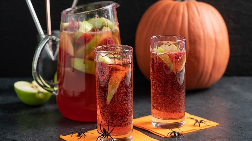 Two glasses of vampire punch on Halloween napkins with a pitcher behind.