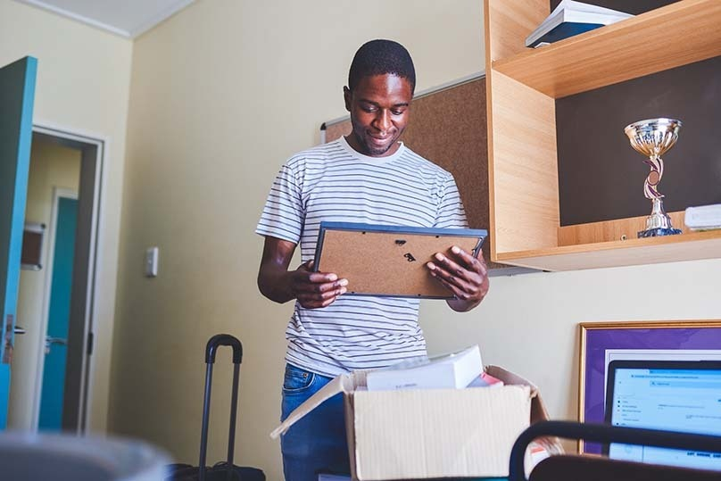 Happy student, dorm room, opening car package, holdling photo from home