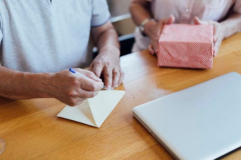 Dad writing note to student, mom holds care package