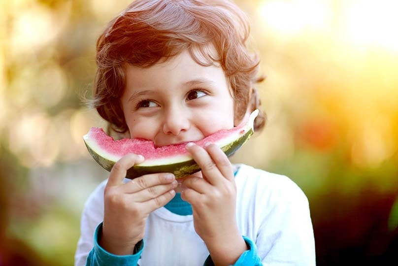 Smiling kid eating watermelon
